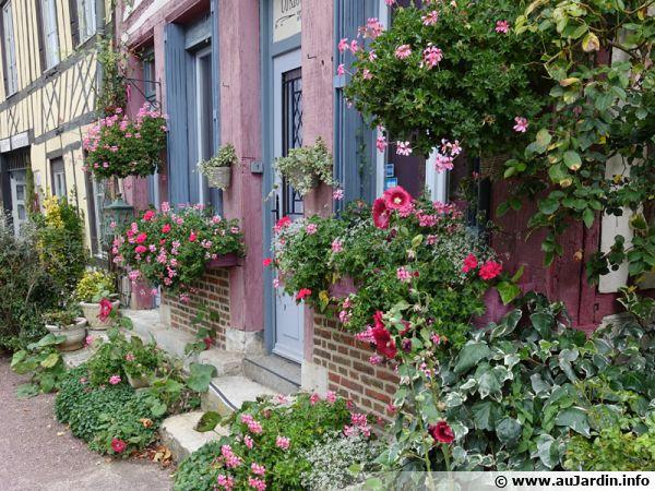 De nombreuses jardinières et pots ornent cette façade de maison