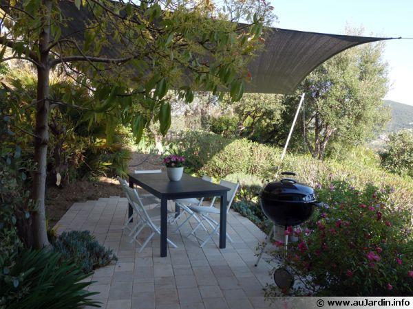 Une terrasse en pierres naturelles protégée par un voile d'ombrage