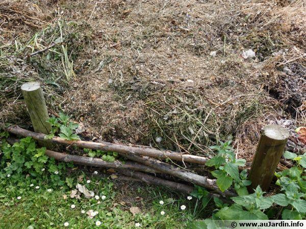 Un compost en tas installé dans un coin du jardin